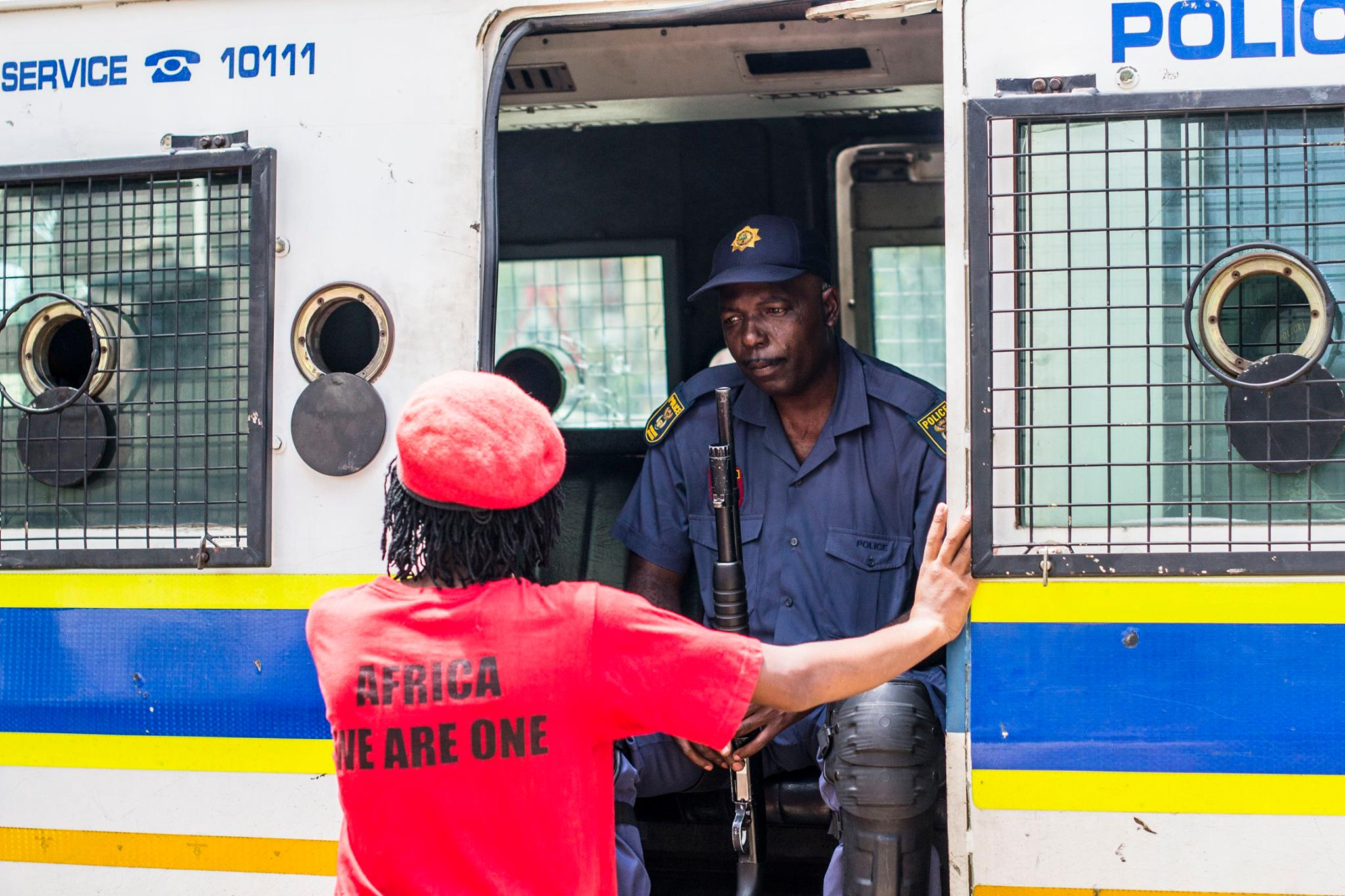 A policeman and protester speak calmly with one another amidst a  confrontation between police and protesters at the University of Pretoria.